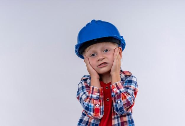 Ein niedlicher kleiner junge mit blondem haar, der kariertes hemd im blauen helm trägt, hält hände auf gesicht auf einer weißen wand