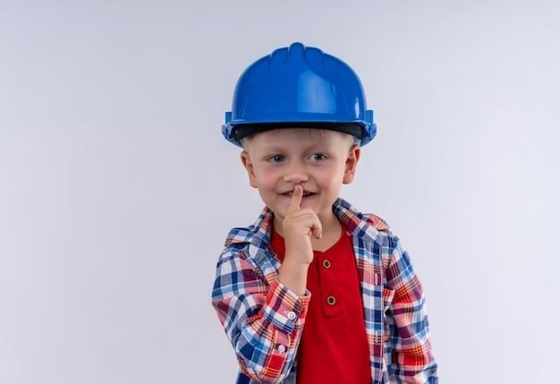 Ein niedlicher kleiner junge mit blondem haar, der kariertes hemd im blauen helm trägt, zeigt shh geste auf einer weißen wand