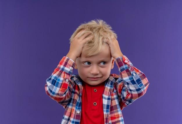 Ein niedlicher kleiner junge mit blondem haar, der kariertes hemd trägt, das hand auf seinem kopf an einer lila wand hält