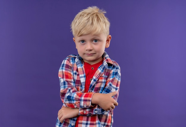 Ein niedlicher kleiner junge mit blondem haar, der kariertes hemd trägt, das mit gefalteten händen auf einer lila wand schaut