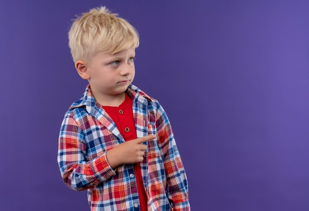 Ein niedlicher kleiner junge mit blondem haar, der kariertes hemd trägt, das mit zeigefinger auf etwas auf einer lila wand zeigt