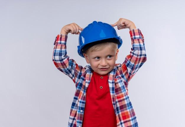 Ein niedlicher kleiner junge mit blondem haar, der kariertes hemd trägt, das mit zeigefinger auf seinen blauen helm auf einer weißen wand zeigt