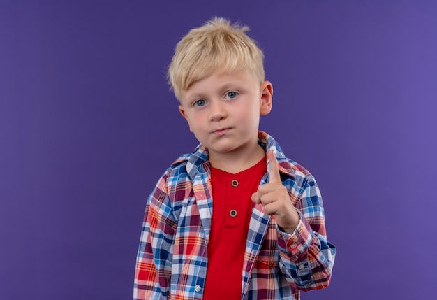 Ein niedlicher kleiner junge mit blondem haar, der kariertes hemd trägt, das zeigefinger zeigt, während auf einer lila wand schaut