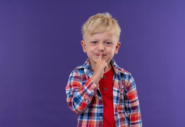 Ein niedlicher kleiner junge mit blondem haar, der kariertes hemd trägt und zeigefinger auf seinem mund hält, der shh geste auf einer lila wand ausdrückt