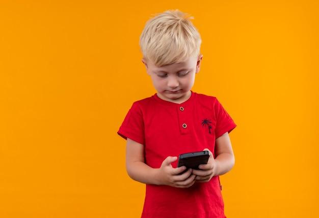 Ein niedlicher kleiner junge mit blondem haar, der rotes t-shirt trägt, das handy auf einer gelben wand betrachtet