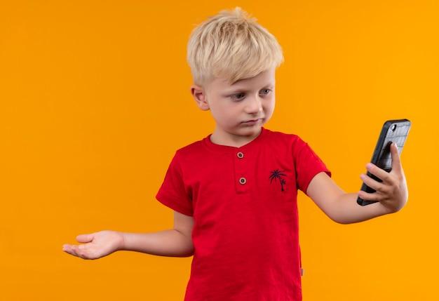 Ein niedlicher kleiner junge mit blondem haar, der rotes t-shirt trägt, das handy mit offener hand auf einer gelben wand betrachtet