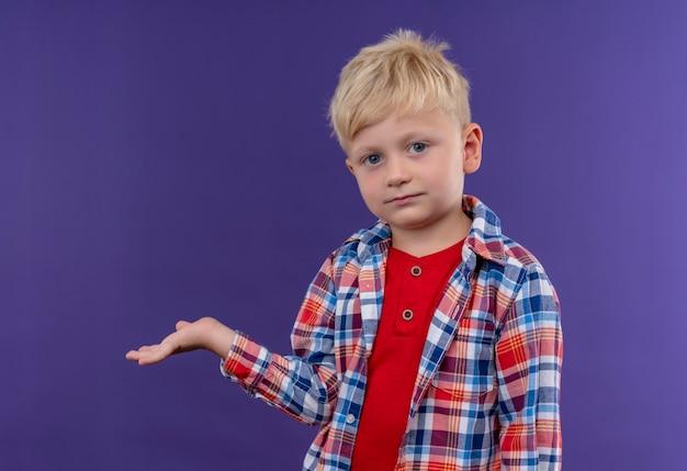 Ein niedlicher kleiner junge mit blondem haar trägt kariertes hemd, das hand anhebt, während auf einer lila wand schaut