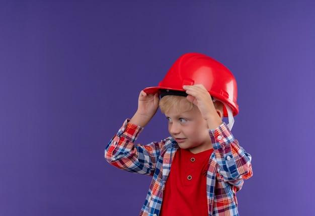 Ein niedlicher kleiner junge mit blondem haar trägt kariertes hemd, das hand auf rotem helm hält, während seite auf einer lila wand schaut