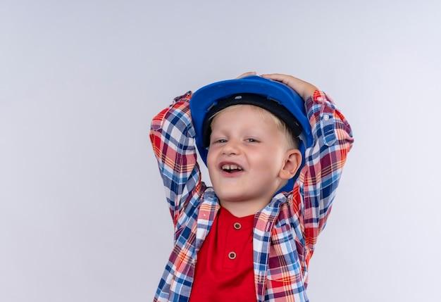 Ein niedlicher kleiner junge mit blondem haar trägt kariertes hemd im blauen helm, der hände auf seinem kopf auf einer weißen wand hält
