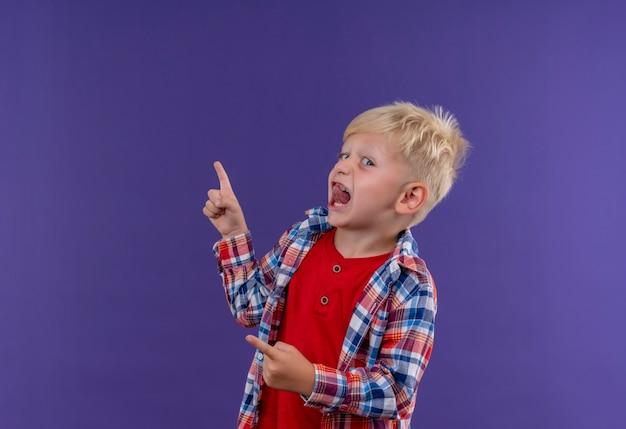 Ein niedlicher kleiner junge mit den blonden haaren, die das karierte hemd tragen, während sie auf eine lila wand zeigen