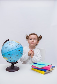 Ein niedlicher student sitzt an einem tisch mit lehrbüchern und einem globus