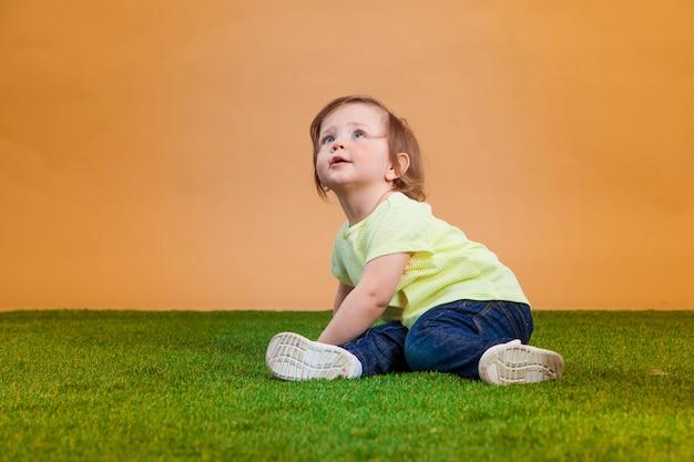 Ein niedliches baby auf orange hintergrund