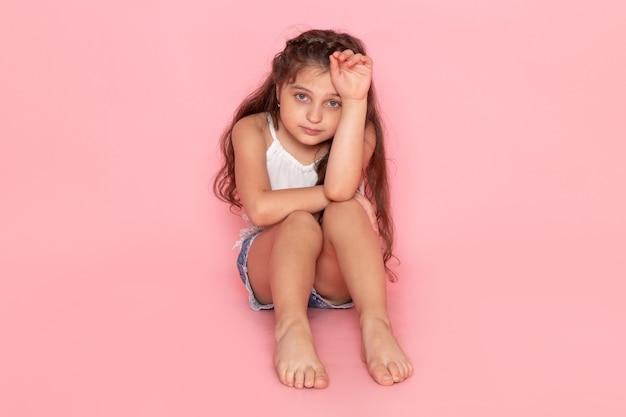 Ein niedliches kleines kind der vorderansicht, das mit gestresstem ausdruck sitzt