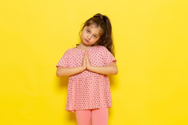 Ein niedliches kleines kind der vorderansicht im rosa kleid, das aufwirft