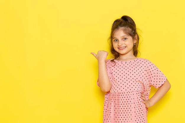 Ein niedliches kleines kind der vorderansicht im rosa kleid, das lächelt und aufwirft