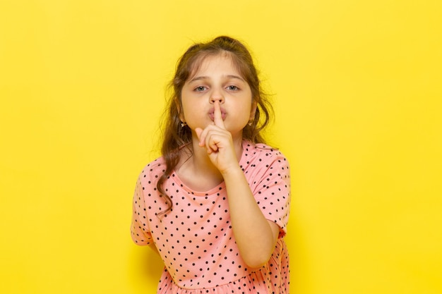 Ein niedliches kleines kind der vorderansicht im rosa kleid, das schweigenzeichen zeigt