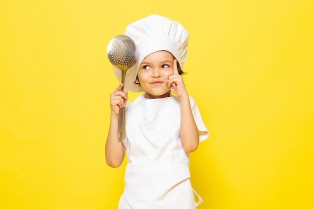 Ein niedliches kleines kind der vorderansicht im weißen kochanzug und in der weißen kochkappe, die großen löffel auf dem gelben wandkind-kochküchenessen halten