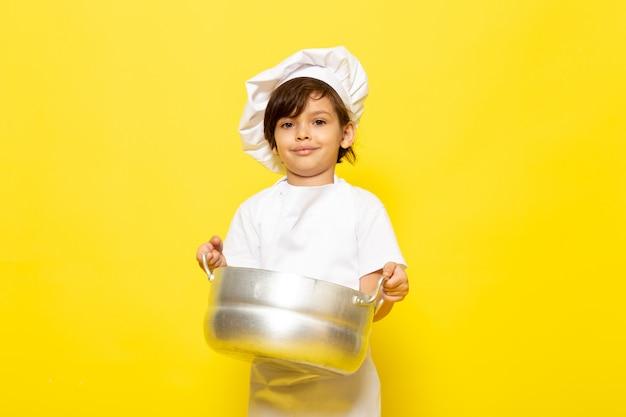 Ein niedliches kleines kind der vorderansicht im weißen kochanzug und in der weißen kochkappe, die silberne pfanne hält, die auf dem gelben wandkind kocht, kocht essen