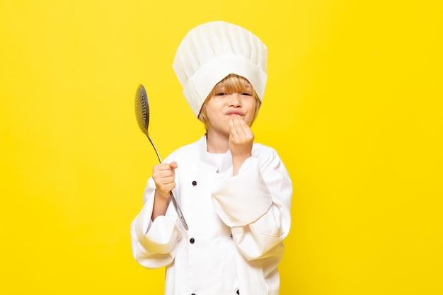 Ein niedliches kleines kind der vorderansicht im weißen kochanzug und in der weißen kochkappe, die silbernen löffel auf dem gelben wandkind-kochküchenessen halten