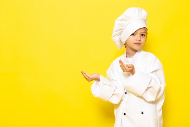 Ein niedliches kleines kind der vorderansicht im weißen kochanzug und in der weißen kochmütze, die auf dem gelben wandkind kocht, kocht essen