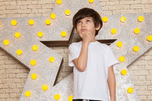 Ein niedliches kleines kind der vorderansicht in den dunklen jeans des weißen t-shirts auf dem stern gestaltete gelben stand und hellen hintergrund