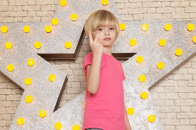 Ein niedliches kleines kind der vorderansicht in den grauen jeans des rosa t-shirts auf dem stern gestaltete gelben stand und hellen hintergrund