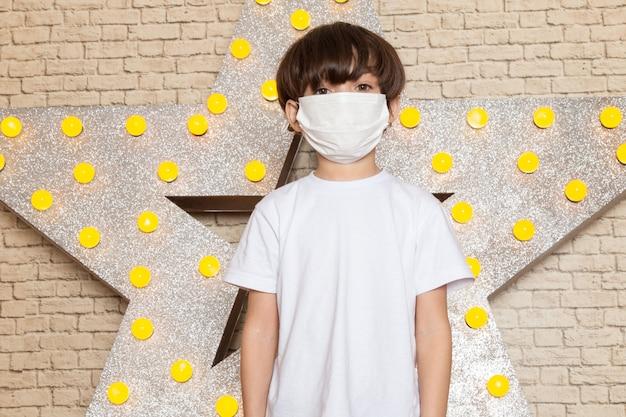 Ein niedliches kleines kind der vorderansicht in der weißen sterilen maske der weißen jeans des weißen t-shirts auf dem stern gestaltete gelben stand und hellen hintergrund