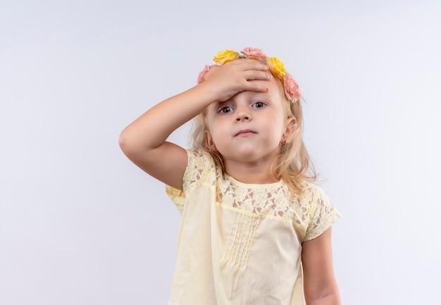 Ein niedliches kleines mädchen, das gelbes hemd im blumenstirnband trägt hand auf kopf auf einer weißen wand hält