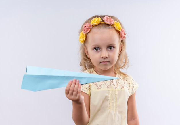 Ein niedliches kleines mädchen, das gelbes hemd im fliegenden papierflugzeug des floralen stirnbandes trägt, während auf einer weißen wand schaut