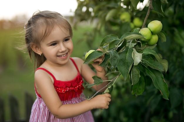 Ein niedliches lächelndes mädchen steht an einem baum mit unreifen grünen äpfeln