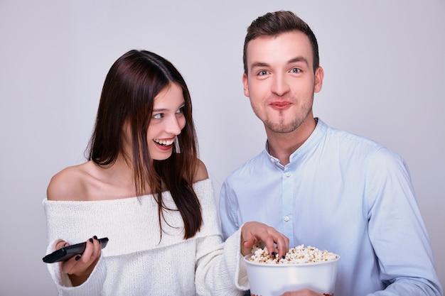 Ein niedliches paar, das karamellpopcorn isst und in einem lustigen moment lacht