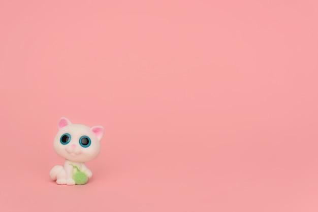 Ein niedliches weißes kätzchen mit einem fadenball auf einem rosa hintergrund. kinderspielzeugkatze mit großen blauen augen und einem fadenballen in seinen pfoten auf rosa. platz für text. minimalismus. nähen, handarbeiten für kinder.