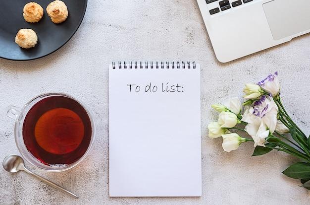 Ein notizblock für die tägliche planung mit frühstücks-laptop und blumen
