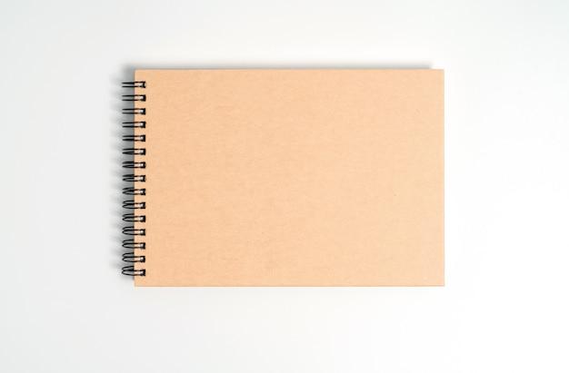 Ein notizbuch auf einer feder. isoliert auf weißem hintergrund.