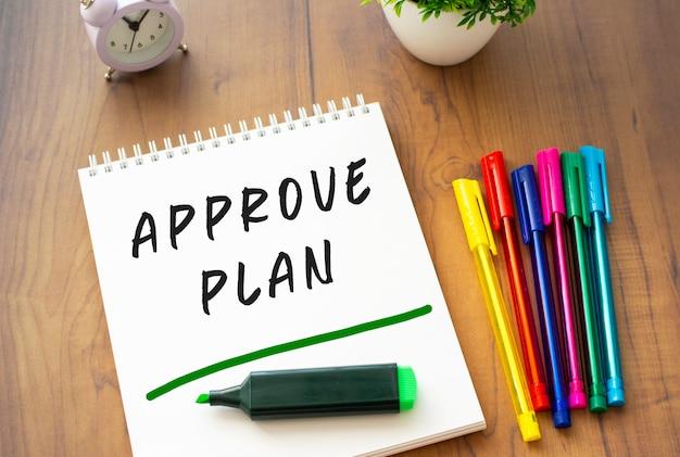 Ein notizbuch auf einer feder mit dem text approve plan auf einem weißen blatt liegt auf einem braunen holztisch mit farbigen stiften.