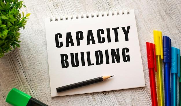 Ein notizbuch auf einer feder mit dem text kapazitätsgebäude auf einem weißen blatt liegt auf einem holztisch mit farbigen stiften