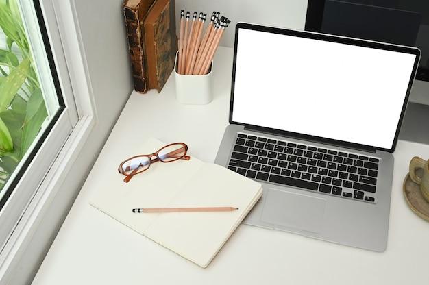 Ein notizbuch, bleistifte, ein buch und ein computer-laptop mit leerem bildschirm stehen auf einem weißen schreibtisch