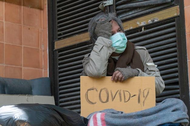 Ein obdachloser trägt ein covid-19-zeichen, ein problem der modernen megastädte.