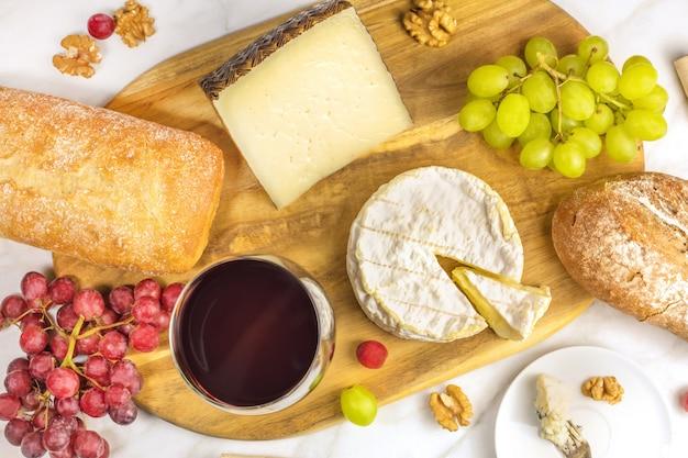 Ein obenliegendes foto eines glases rotweins mit käse