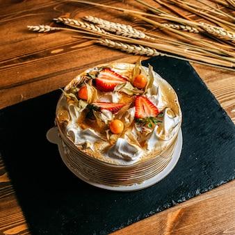 Ein obstkuchen mit draufsicht, köstlich dekoriert mit geschnittenen erdbeeren rund um weiße platte
