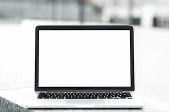 Ein offener Laptop, der leere weiße Bildschirmanzeige auf Bank gegen unscharfen Hintergrund zeigt