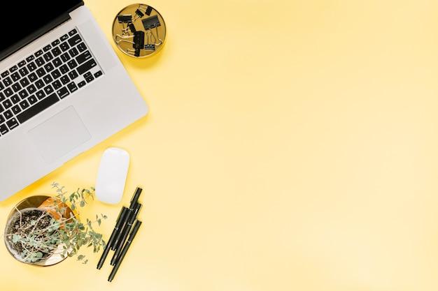 Ein offener laptop; maus mit bulldogge büroklammern und filzstifte auf gelbem hintergrund