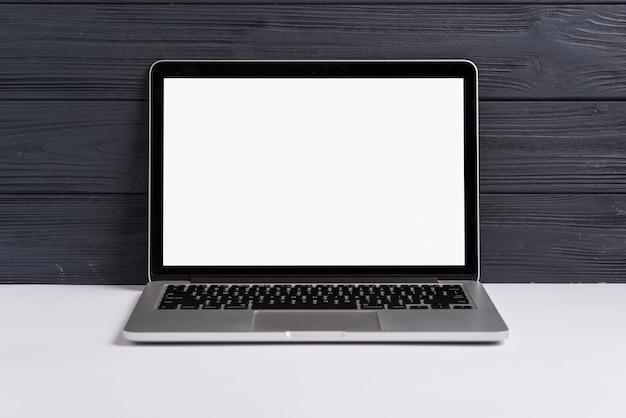 Ein offener laptop mit leerem weißem bildschirm auf weißem schreibtisch gegen schwarzen hölzernen hintergrund
