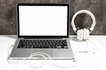 Ein offener Laptop mit weißem Kopfhörer auf Schreibtisch gegen Betonmauer