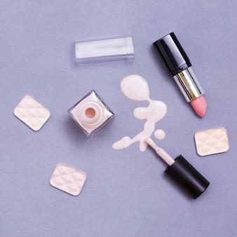 Ein offener lippenstift; nagellackflasche und lidschatten auf lila hintergrund