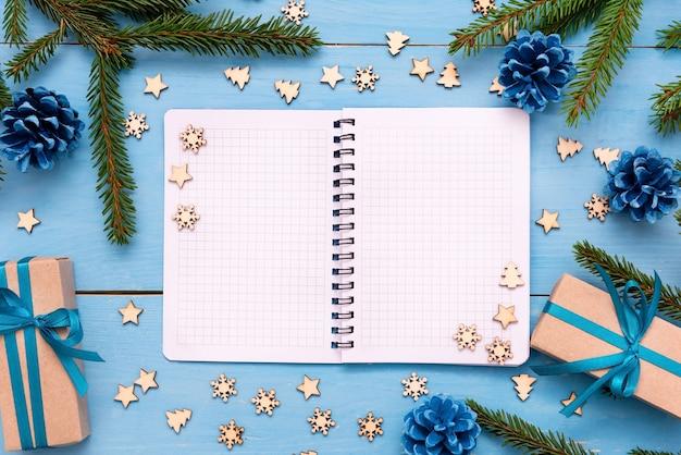 Ein offener notizblock zum schreiben auf einem blauen tisch mit weihnachtsgeschenken. flach liegen