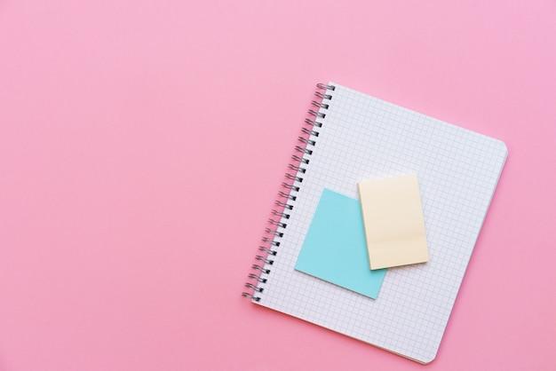 Ein offener spiralnotizblock mit aufklebern, die auf dem oberen briefpapier auf rosa hintergrund liegen