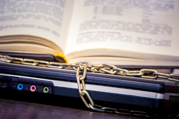 Ein offenes buch liegt auf einem laptop, der durch eine kette verbunden ist