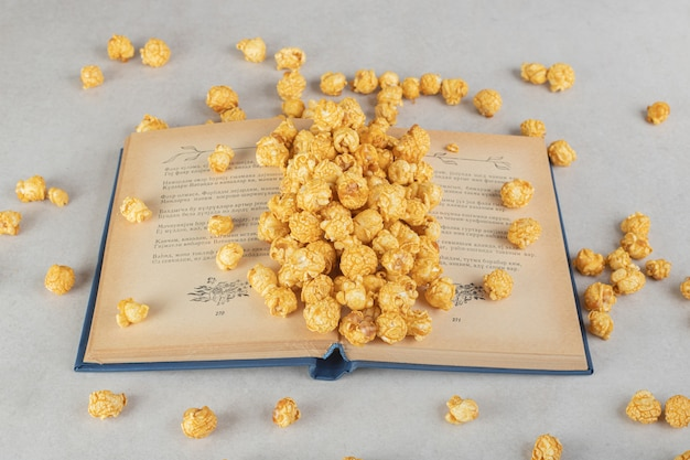 Ein offenes buch mit einem haufen karamellbeschichtetem popcorn auf marmor.