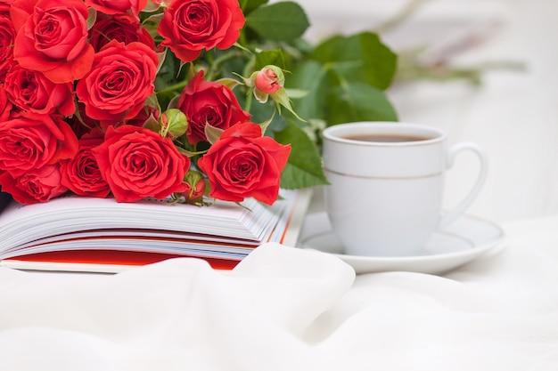 Ein offenes buch mit rot-orangefarbenen rosen. lesen und entspannen. romantisches, süßes dating-konzept.
